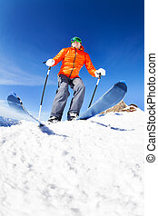 Active young man ready to skiing view from below during...