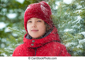 Happy boy with falling snow in the forest