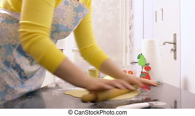 Woman making dough with rolling pin in kitchen.