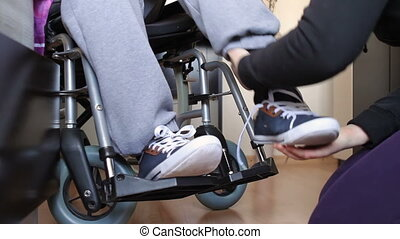 Helping a disabled young man in wheelchair get dressed