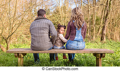 Angry little girl looking to the camera sitting on bench