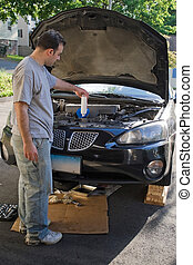 Man Changing the Oil - A young man adding oil to his car at...