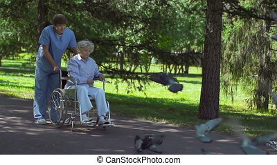 Feeding Birds - Handicapped woman and her doctor feeding...