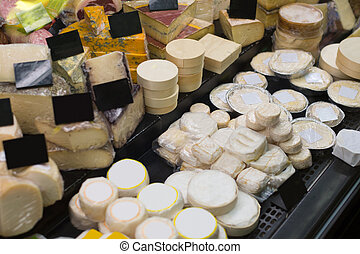Market counter with fresh cheese kinds close up