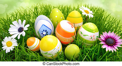 Easter eggs and flowers on grass