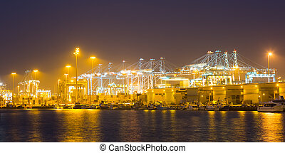 night view of cranes and containers in cargo seaport...