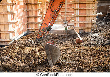 Close up of excavator scoop digging earth at construction...