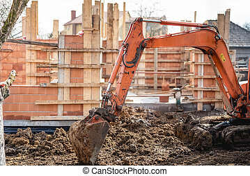 track-type excavator loader working on earth and loading at house construction site