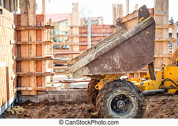 Dumper truck unloading gravel, sand and stones at...