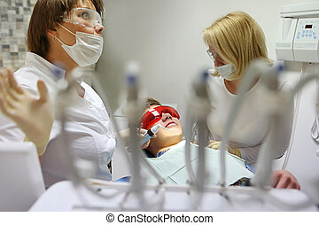 Doctor and nurse perform the procedure for dental treatment...