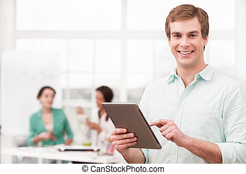 Young smiling businessman using tablet computer