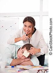 Mixed race businesswoman gluing sticker on sleeping man -...