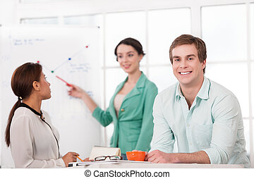 Young smiling businessman and his creative team working with diagram