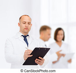 serious male doctor with clipboard - medicine, profession,...