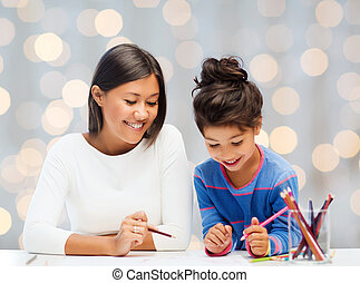 happy mother and daughter drawing with pencils - family,...