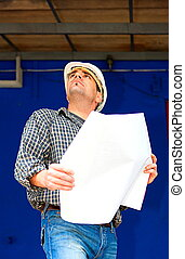 Engineer with blueprint on construction site