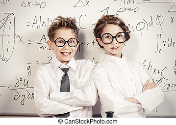 science - Two students standing by the school board in the...