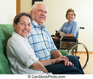 Parents and daughter in wheelchair - Happy mature couple and...