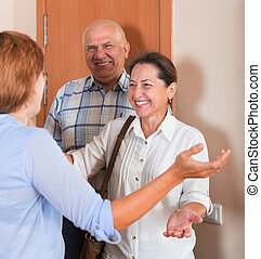 Meeting parents - Young woman meeting mature friends at the...