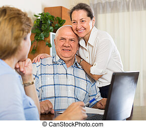 Senior couple with social worker at home - Smiling senior...