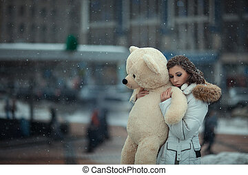 Girl with a bear during snow - City, snowing, there is a...