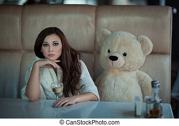 Sad girl at the table with a toy bear. - Sad girl sits at a...