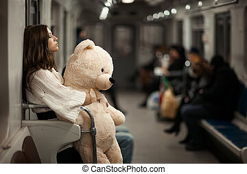 Girl with bear in a subway car. - Sad girl hugged her toy...