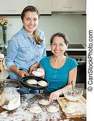 two women - Mature mother with adult daughter making meat...