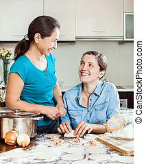 cooking mother with adult daughter