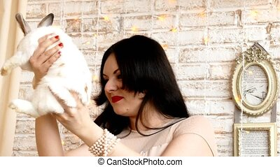 Brunette woman hold the rabbit