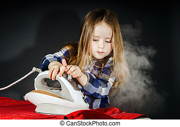 Cute little girl helping your mother by ironing clothes,...