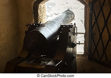 Ancient cannon pointing through embrasure at ancient castle...