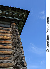 Cornice of old wooden house on blue sky background