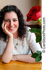 Young attractive woman sitting next to a red rose