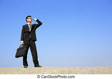 Successful business man purposefully looking away with blue...