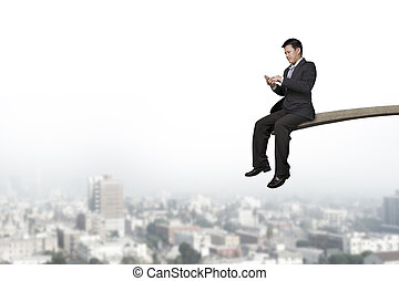 Using mobile phone businessman sitting on springboard with...