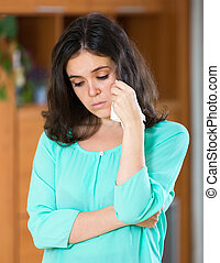 woman crying at home - Young brunette woman crying at home...