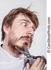 Young bearded man with scissors