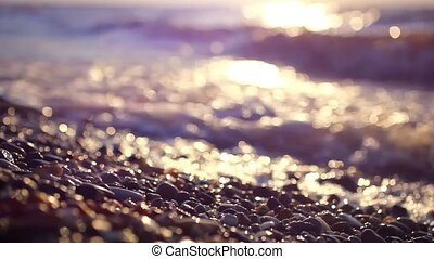 colorful pebbles on the beach at amazing sunset with sea view, splashes waves and sunlight. blur And change of focus. HD. 1920x1080