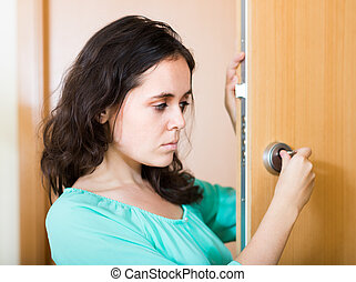 Brunette looking at broken lock of door