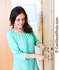 brunette unlocking outer door - Young adult brunette...