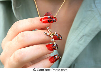 Nail-art fingers holding golden cross with necklace.