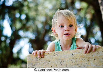 surprised toddler girl looking right in camera shallow focus...