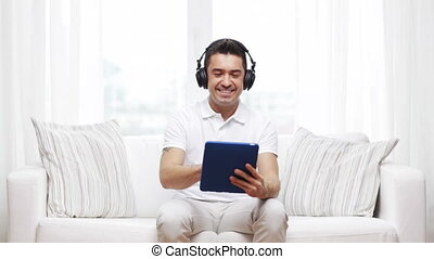 smiling man with tablet pc and headphones at home -...