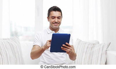 smiling man working with tablet pc at home - technology,...
