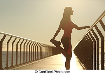Runner silhouette doing stretching exercises at sunset in a...
