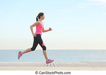 Side view of a woman running on the beach with the horizon...