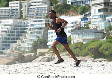 Young man exercise running on the beach - Active young man...