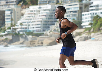 Young african american man running at the beach - Healthy...