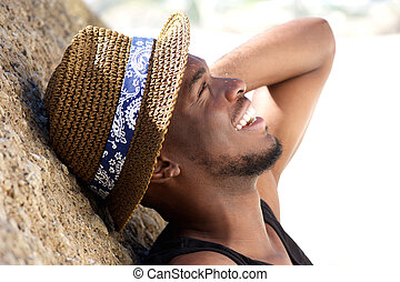 Cheerful young man laughing at the beach with hat - Close up...